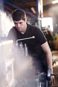 Mechanic working at machinery in auto repair shopの写真素材 [FYI02168302]
