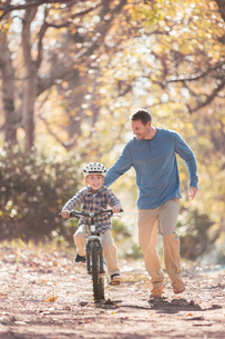 Father teaching son to ride a bicycle on path in woodsの写真素材 [FYI02168307]