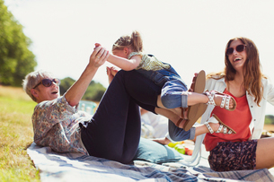 Playful grandmother and granddaughter on blanket in sunny fieldの写真素材 [FYI02168331]