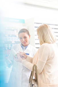 Pharmacist and customer reviewing label on bottle in pharmacyの写真素材 [FYI02168334]