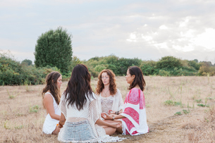 Boho women meditating in circle in rural fieldの写真素材 [FYI02168335]