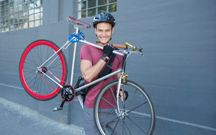 Portrait smiling young man carrying bicycle on urban sidewalkの写真素材 [FYI02168342]