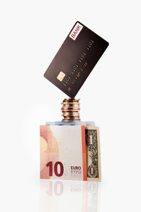 Credit card balancing on coins and cashの写真素材 [FYI02168348]