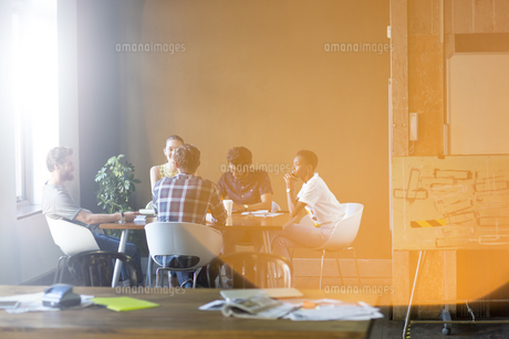 Lens flare over creative business people meeting at office tableの写真素材 [FYI02168353]