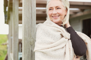 Smiling senior woman wearing shawl on porchの写真素材 [FYI02168361]