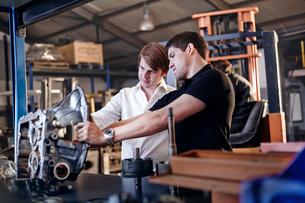 Mechanic and customer examining part in auto repair shopの写真素材 [FYI02168376]