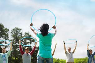 Team holding plastic hoops overheadの写真素材 [FYI02168378]