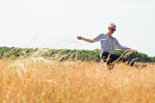 Playful senior woman dancing in sunny rural fieldの写真素材 [FYI02168417]