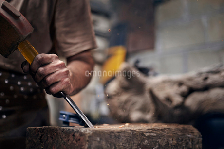 Blacksmith chiseling wood in workshopの写真素材 [FYI02168425]