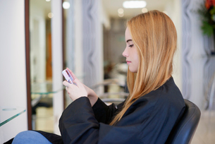 Woman texting with cell phone in hair salonの写真素材 [FYI02168437]