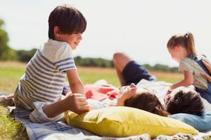 Family relaxing on blanket in sunny fieldの写真素材 [FYI02168441]