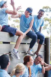 Team celebrating at wall on boot camp obstacle courseの写真素材 [FYI02168449]