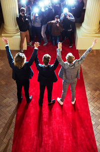Celebrities holding hands with arms raised for paparazzi photographers at red carpet eventの写真素材 [FYI02168457]