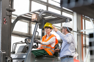 Supervisor directing worker driving forklift in factoryの写真素材 [FYI02168470]