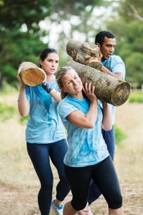 Determined woman running with log on boot camp obstacle courseの写真素材 [FYI02168483]