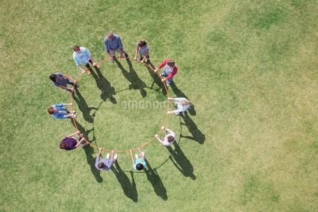 Overhead view of team connected in circle around plastic hoopの写真素材 [FYI02168484]