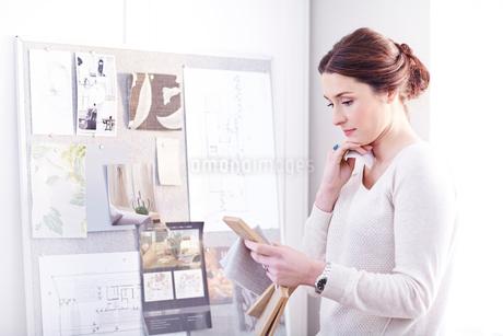 Interior designer viewing swatches in officeの写真素材 [FYI02168524]