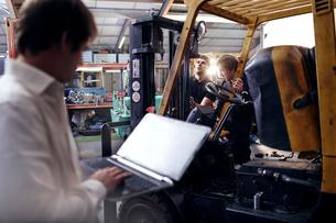 Mechanic using laptop next to forklift in auto repair shopの写真素材 [FYI02168526]