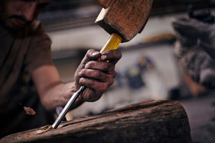 Close up of blacksmith chiseling wood with toolの写真素材 [FYI02168624]