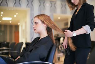 Hairdresser preparing to cut customer's long hair in salonの写真素材 [FYI02168629]