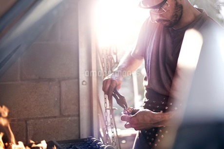 Blacksmith using pliers at fire in forgeの写真素材 [FYI02168661]