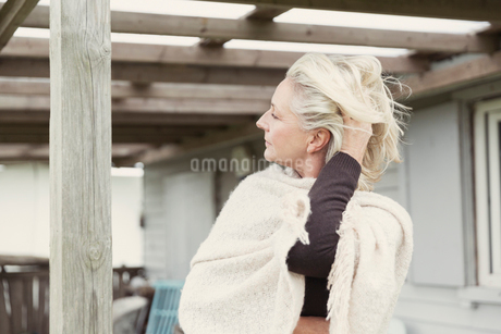 Senior woman with hand in hair wearing shawl on porchの写真素材 [FYI02168665]