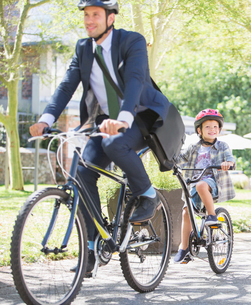 Businessman in suit and helmet riding tandem bicycle with sonの写真素材 [FYI02168677]