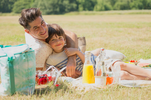 Portrait affectionate father and son relaxing on picnic blanket in sunny fieldの写真素材 [FYI02168683]