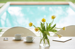 Yellow tulip bouquet and coffee cups on poolside tableの写真素材 [FYI02168699]