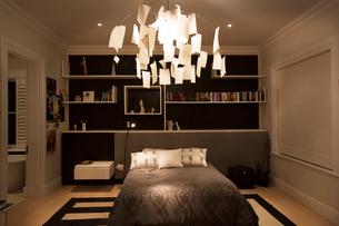 Illuminated modern paper chandelier hanging in bedroomの写真素材 [FYI02168728]