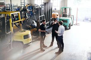 Mechanics talking near forklifts in auto repair shopの写真素材 [FYI02168738]