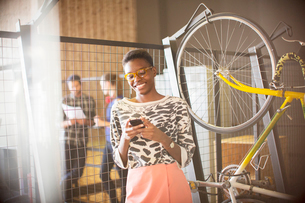 Smiling businesswoman texting on cell phone next to bicycleの写真素材 [FYI02168751]