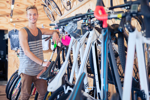 Portrait smiling young man leaning on rack in bicycle shopの写真素材 [FYI02168771]