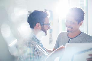 Smiling creative businessmen using digital tablet in sunny officeの写真素材 [FYI02168772]