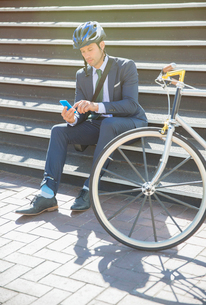Businessman in suit and helmet texting with cell phone next to bicycle on sunny urban stairsの写真素材 [FYI02168781]