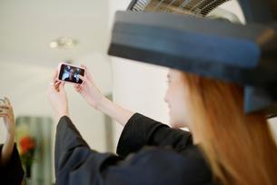 Customer taking selfie with camera phone in hair salonの写真素材 [FYI02168820]