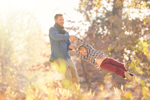 Father spinning son among autumn leavesの写真素材 [FYI02168825]