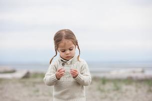Curious girl examining pebbles on beachの写真素材 [FYI02168829]