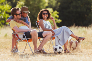 Smiling family relaxing in sunny fieldの写真素材 [FYI02168834]