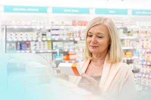 Customer reading label on box in pharmacyの写真素材 [FYI02168865]