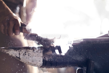Close up of blacksmith brushing iron tool over anvil in forgeの写真素材 [FYI02168872]