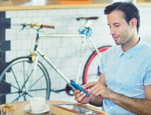 Man texting with cell phone near bicycle in cafeの写真素材 [FYI02168879]
