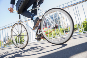 Low section businessman in suit riding bicycle on sunny urban sidewalkの写真素材 [FYI02168899]
