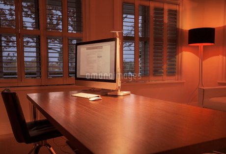 Illuminated lamp behind computer on desk in home officeの写真素材 [FYI02168910]