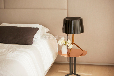 Lamp and rose bouquet on bedside tableの写真素材 [FYI02168915]