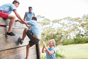 Teammates helping man over wall on boot camp obstacle courseの写真素材 [FYI02168917]