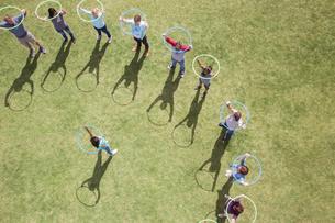 Woman leading team with plastic hoops overheadの写真素材 [FYI02168921]