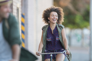 Enthusiastic woman with afro riding bicycleの写真素材 [FYI02168959]