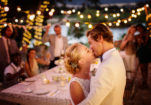 Young couple kissing during wedding reception in domestic gardenの写真素材 [FYI02168968]