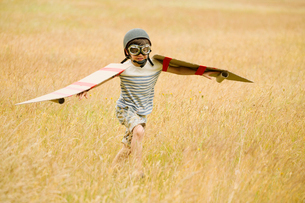 Boy running with wings and aviator's cap and flying goggles in fieldの写真素材 [FYI02168982]